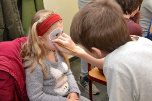 Jakub Naramski aus der Klasse 7a schminkt die fünfjährige Giulia Weidmüller als Schmetterling